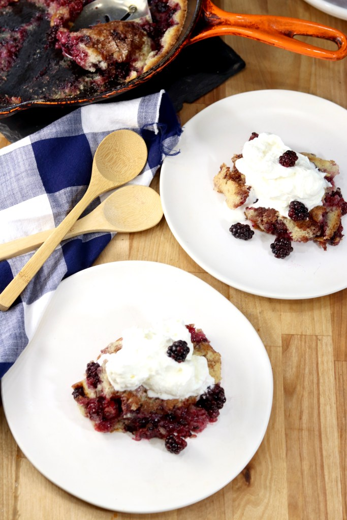 Blackberry Cobbler with whipped cream on 2 white saucers