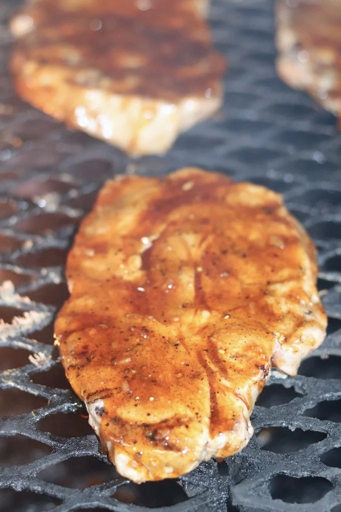 pork steaks on the grill with peach bbq sauce