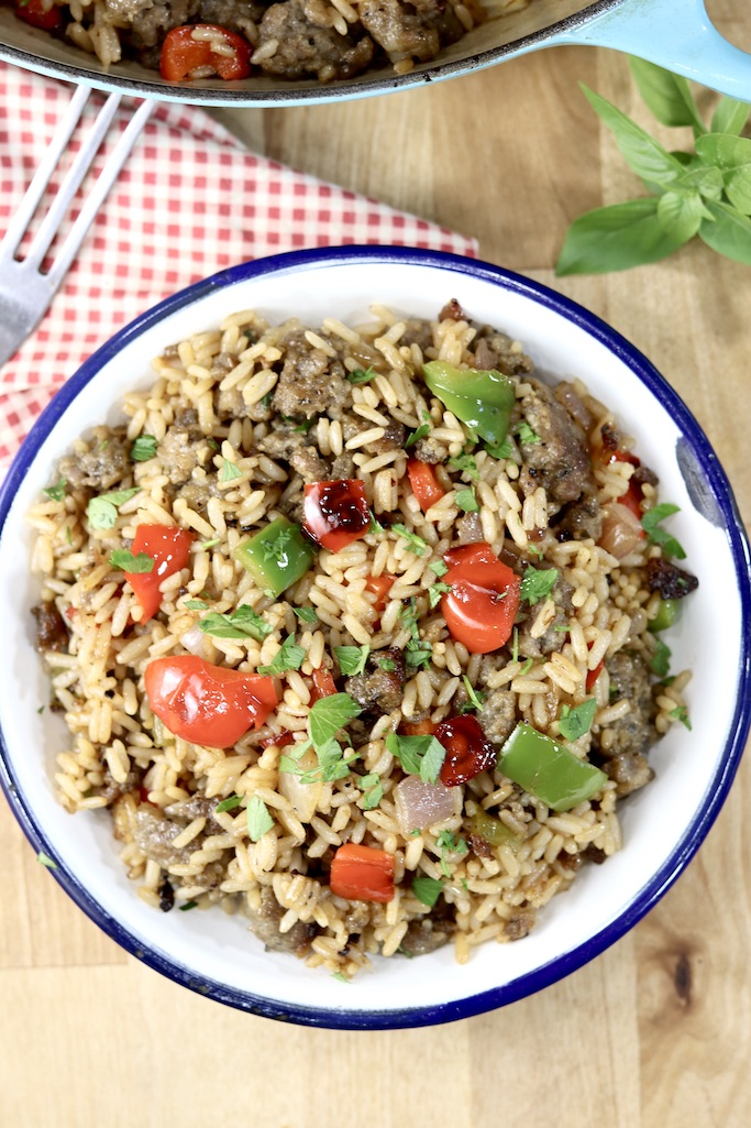 Bowl of sausage and pepper rice garnished with fresh herbs