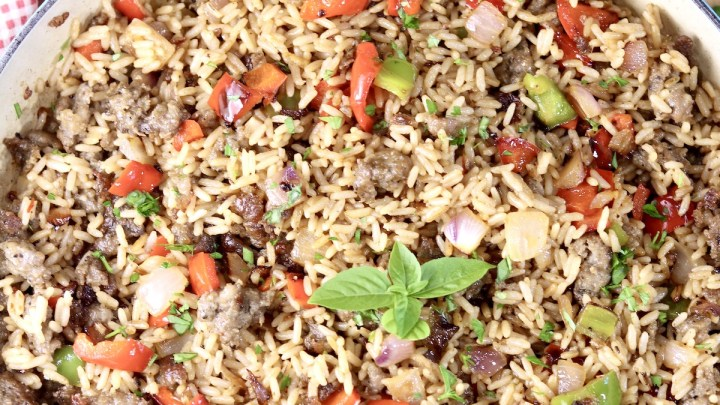 Sausage and Pepper Rice dinner in a large pan, garnished with fresh basil leaves