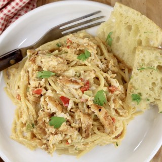Plate of chicken spaghetti and garlic bread with a fork