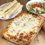 Pan of baked lasagna, platter of breadsticks and bowl of salad topped with tomatoes