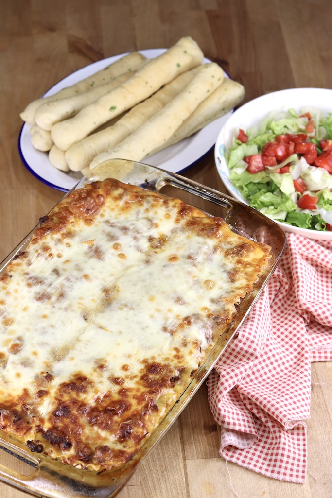 Lasagna in a casserole dish, plate of breadsticks, salad in a bowl with tomatoes, red check napkin