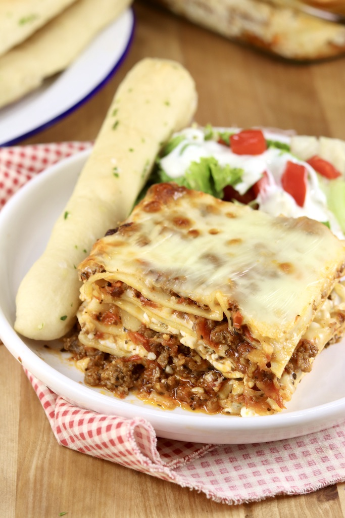 Slice of baked lasagna with a breadstick and salad on a white plate