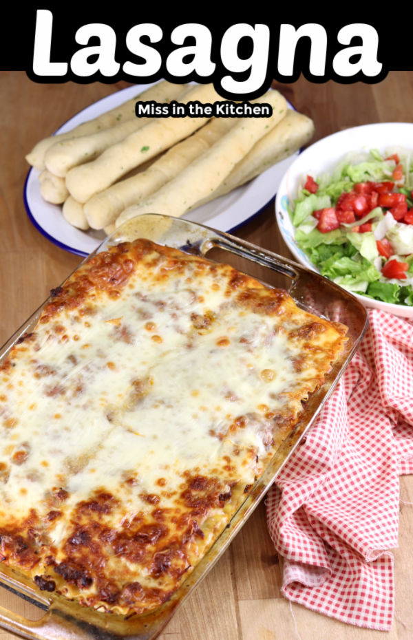 Lasagna text overlay, casserole dish with breadsticks and salad