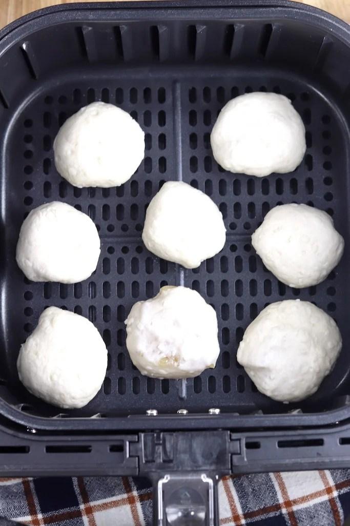 Air fryer basket with 8 apple pie bomb dough
