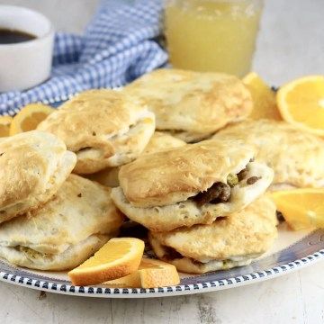 Air Fryer Sausage Biscuits on a platter with orange slices
