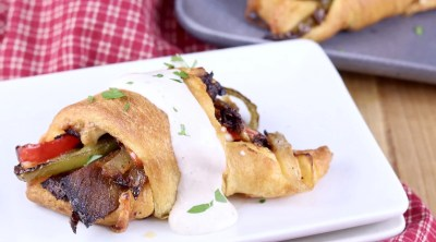 Cheesesteak Crescent Roll Ups with horseradish sauce on a white plate, platter of rolls in back ground. Red check napkin