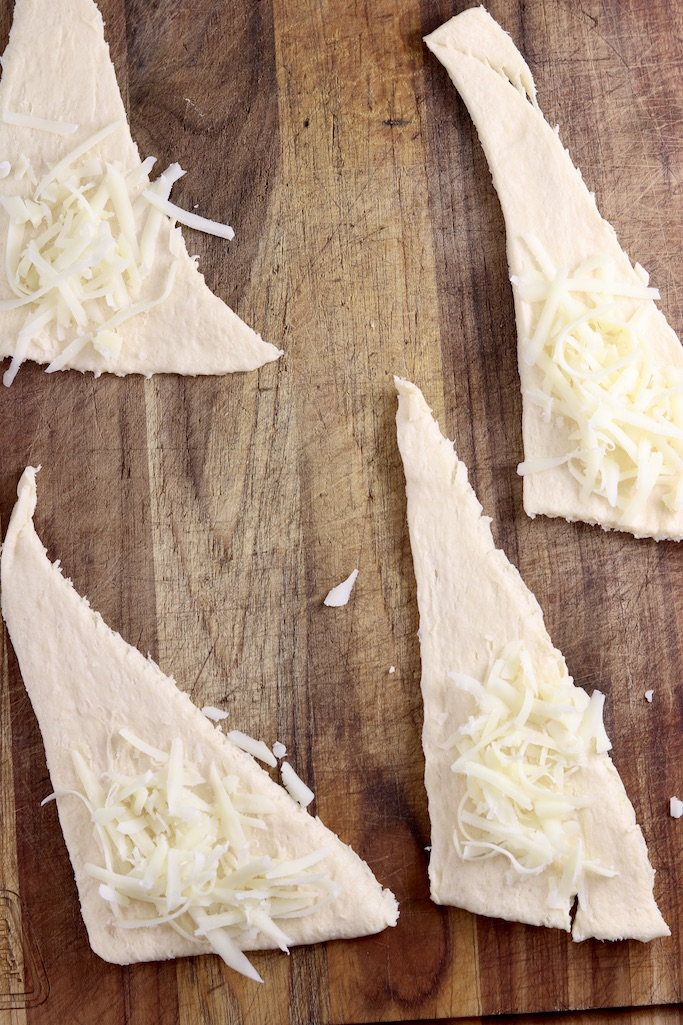 shredded cheese on crescent dough triangles