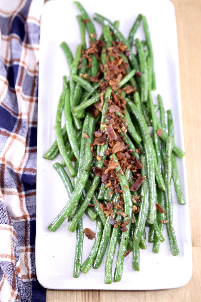 Platter of green beans topped with crispy bacon