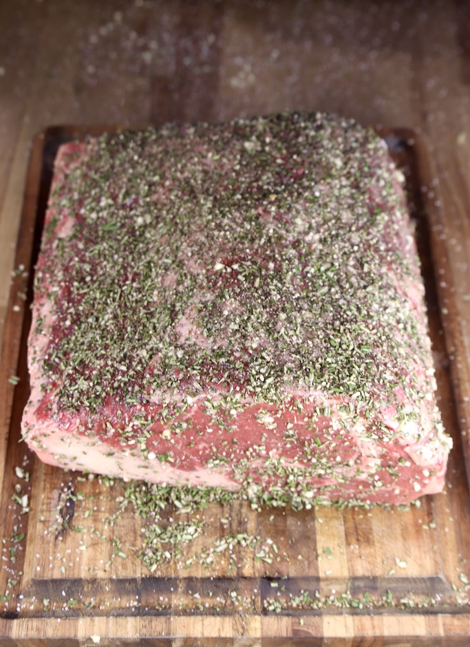 Prime rib roast seasoned with garlic and rosemary rub on a cutting board ready to grill or roast