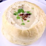 Bread bowl of beer cheese soup topped with bacon and parsley