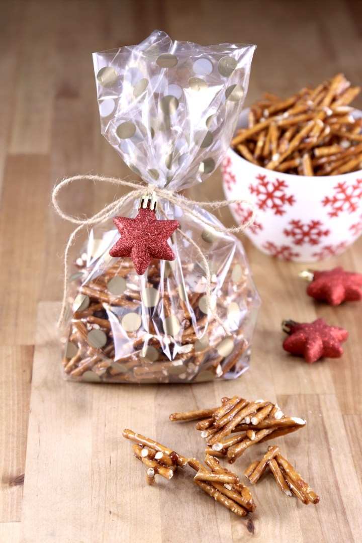 Cellophane bag of candied pretzels tied with string and a red star ornament. A few pretzels on the counter
