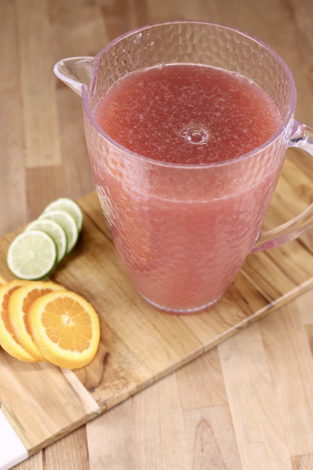 Pitcher of Christmas punch on a wood board with slices of orange and limes.
