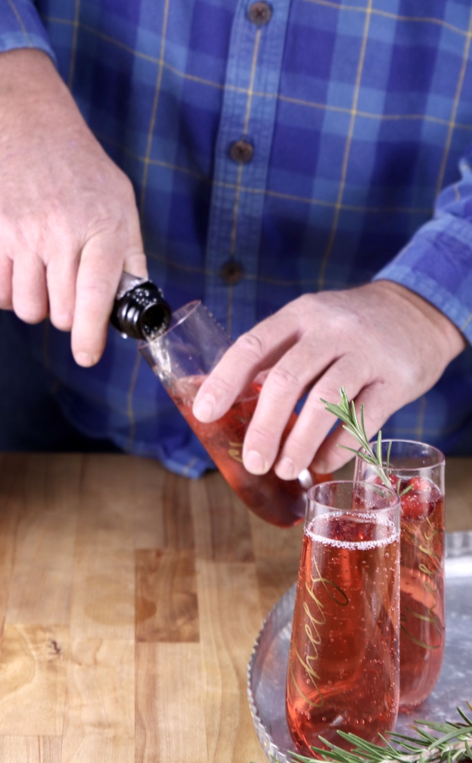 Man filling a champagne flute with sparkling wine for mimosa
