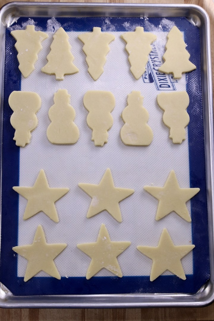 Cookie sheet lined with a silpat. Tree, snowmen and star cut out cookies ready to bake.