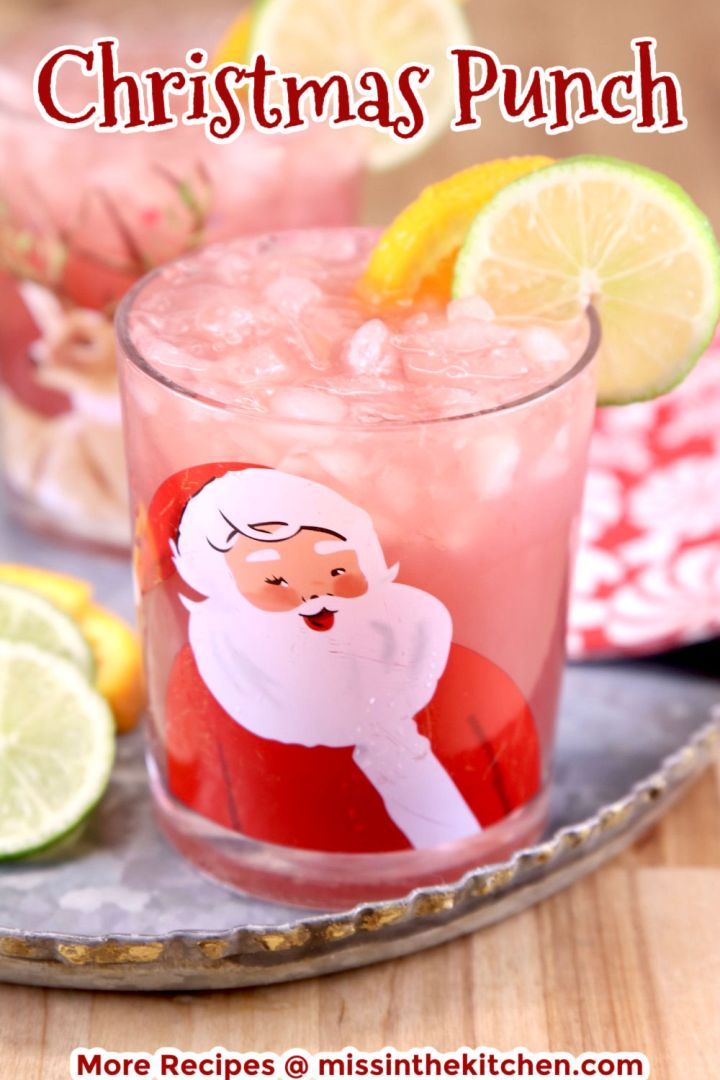 Christmas Punch in a Santa glass with orange and lime garnish - text overlay