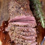 Beef Tenderloin with garlic butter crust, partially sliced on a cutting board