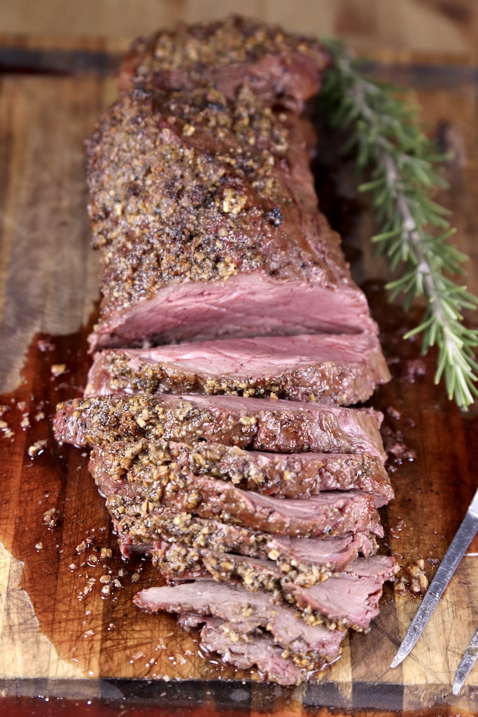 Beef tenderloin on a cutting board, half of the roast sliced. Sprig of rosemary to the side