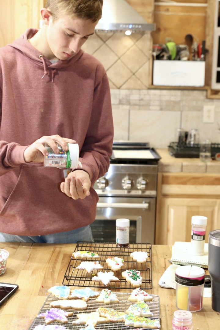 Teenage boy decorating sugar cookies for Christmas in a kitchen