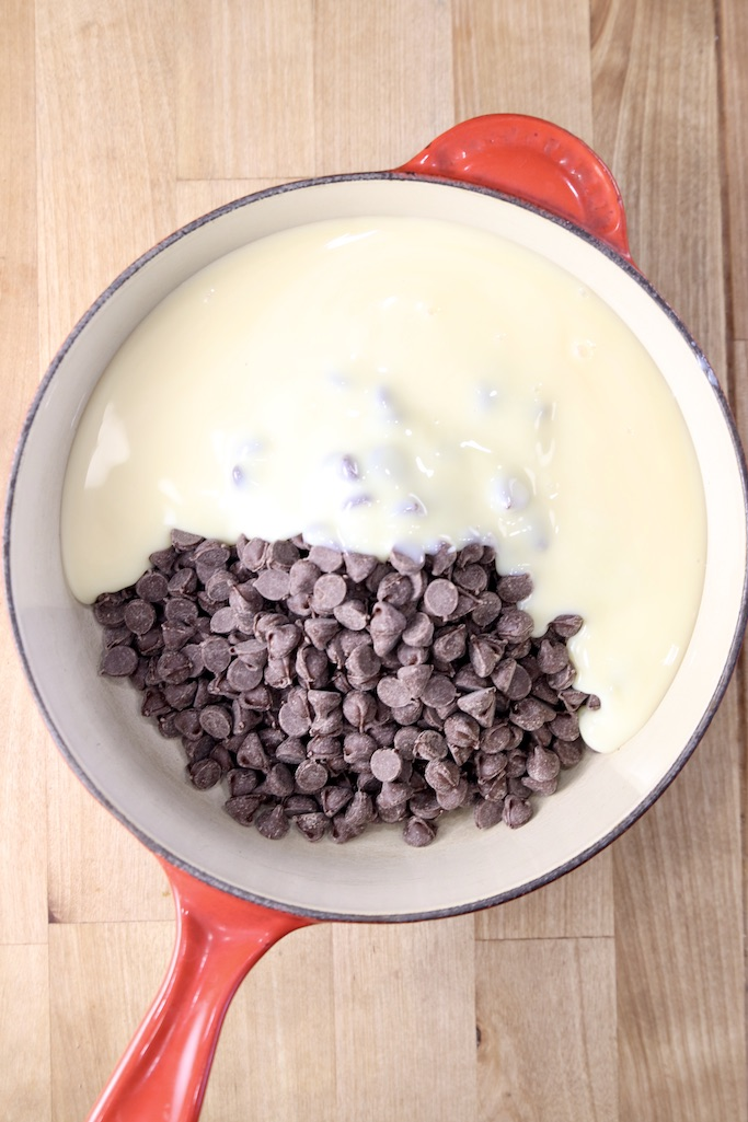 Red saucepan with chocolate chips and sweetened condensed milk