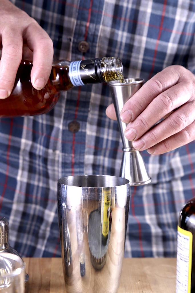 Pouring bourbon into a jigger for cocktails