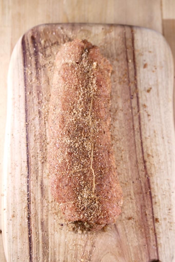 cutting board with pork tenderloin coated in dry rub seasonings