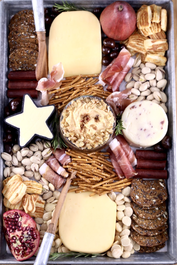Charcuterie board with Bacon beer cheese dip, cheese, nuts and crackers