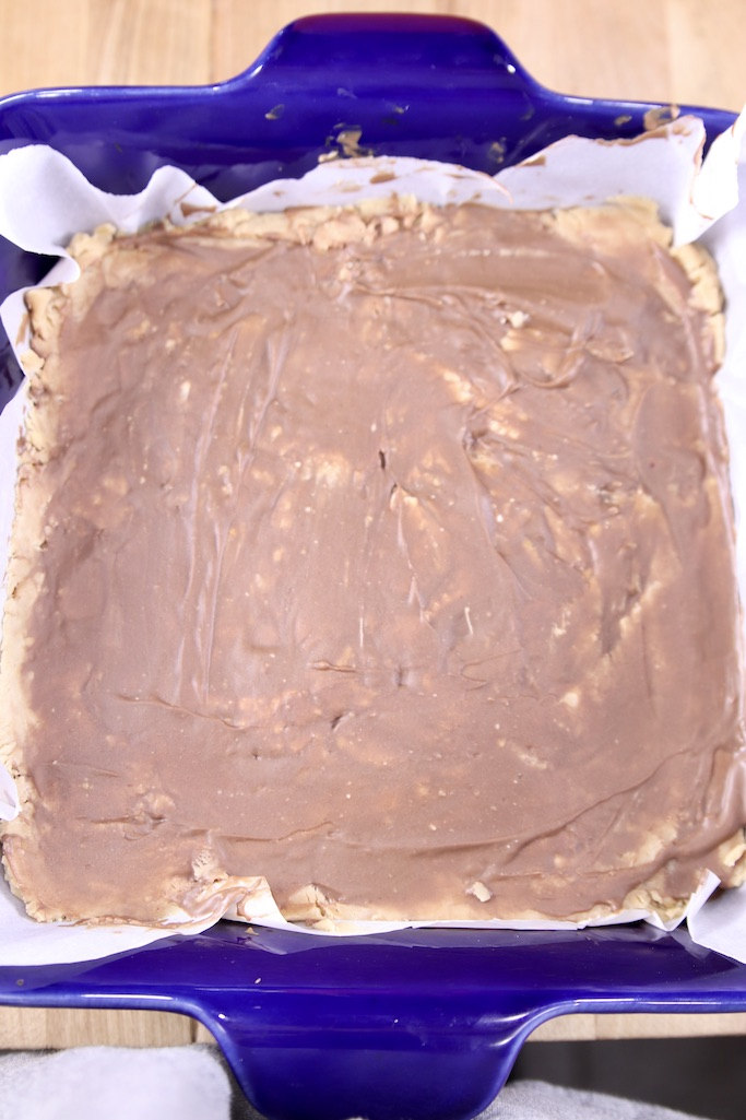 Chilled peanut butter cup fudge with chocolate on top in a blue baking dish