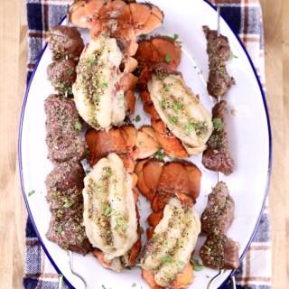 Platter of grilled lobster tails and steak kabobs