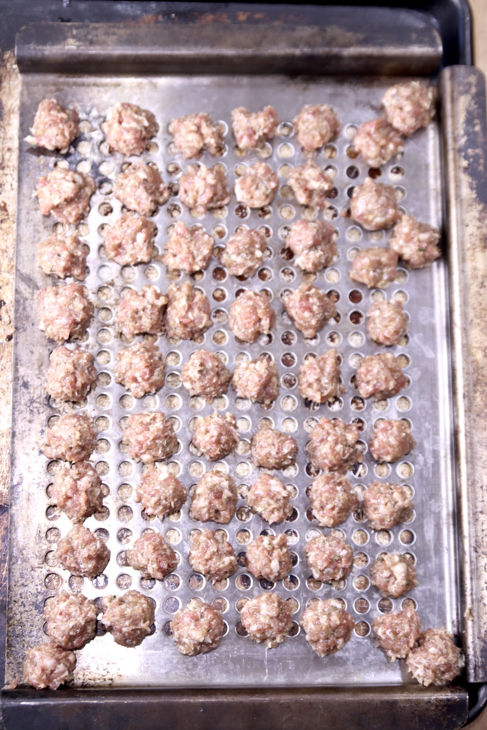 grill pan of raw meatballs