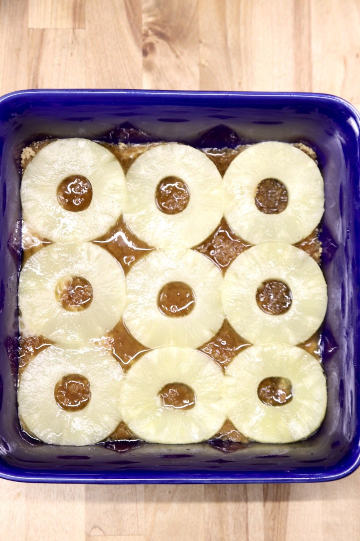 9 pineapple rings over brown sugar mixture in a blue baking dish