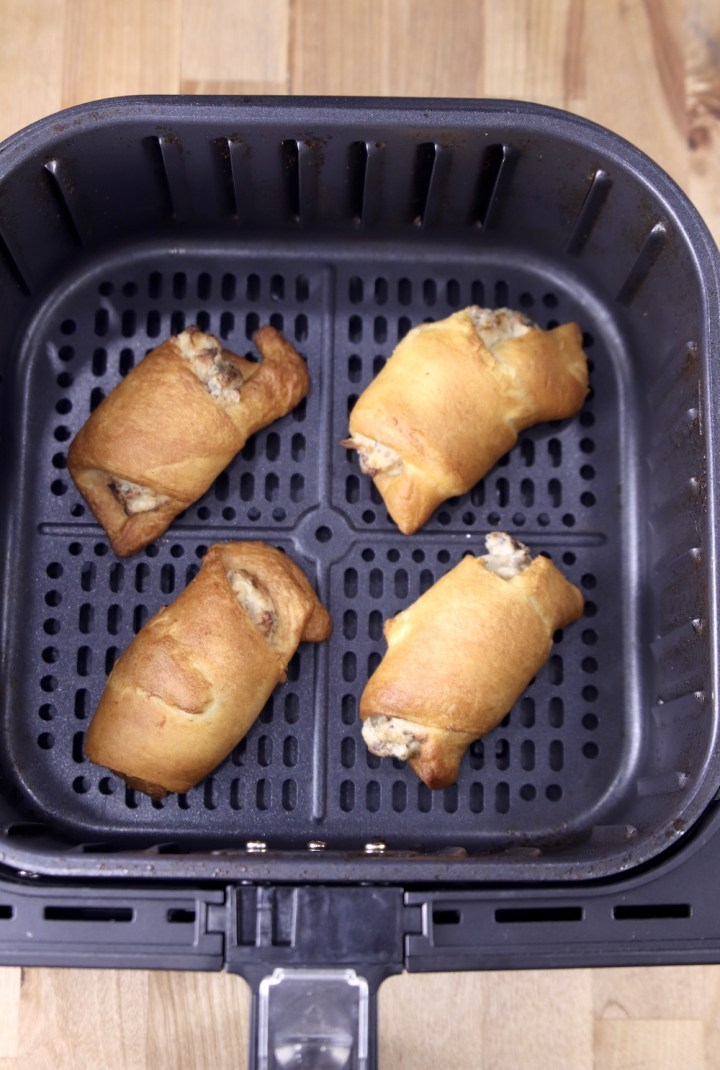 4 cooked sausage cream cheese crescents in air fryer basket