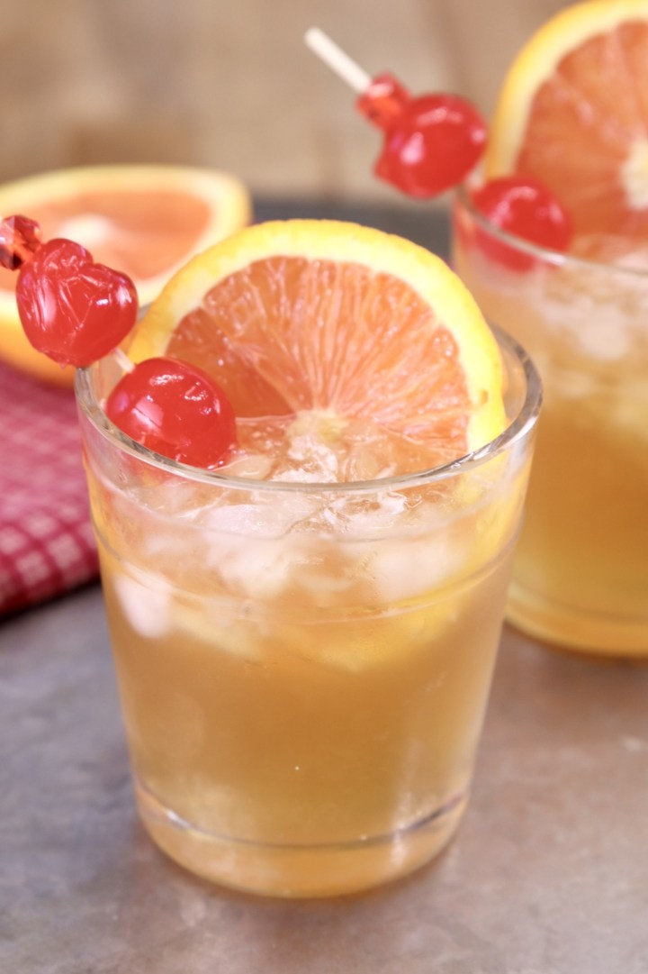 Amaretto Sour Cocktail on a platter with orange slice and cherries