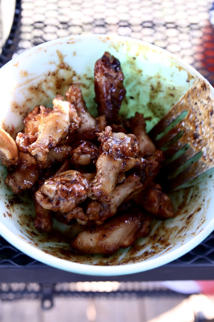 adding maple glaze to bowl of wings