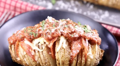 Shallow black bowl with a hasselback potato topped with pizza sauce and cheese