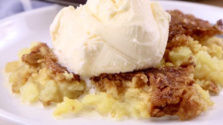 plate of pineapple dump cake served with vanilla ice cream