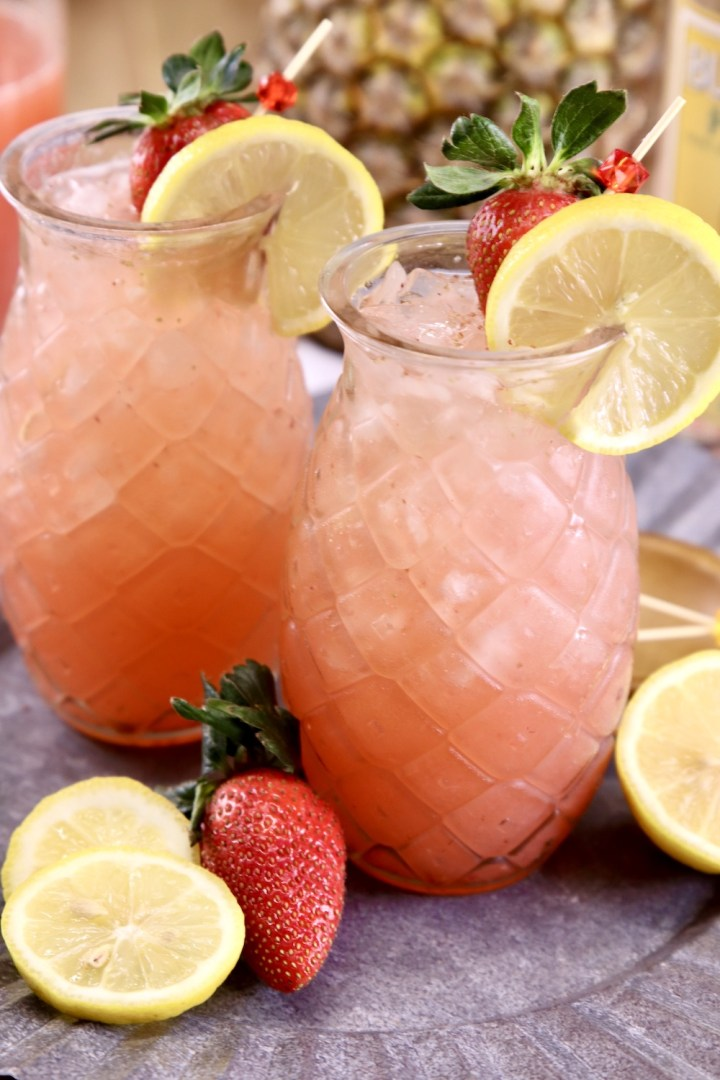 Pineapple Vodka Strawberry Lemonade Cocktails in tiki glasses with lemon garnish