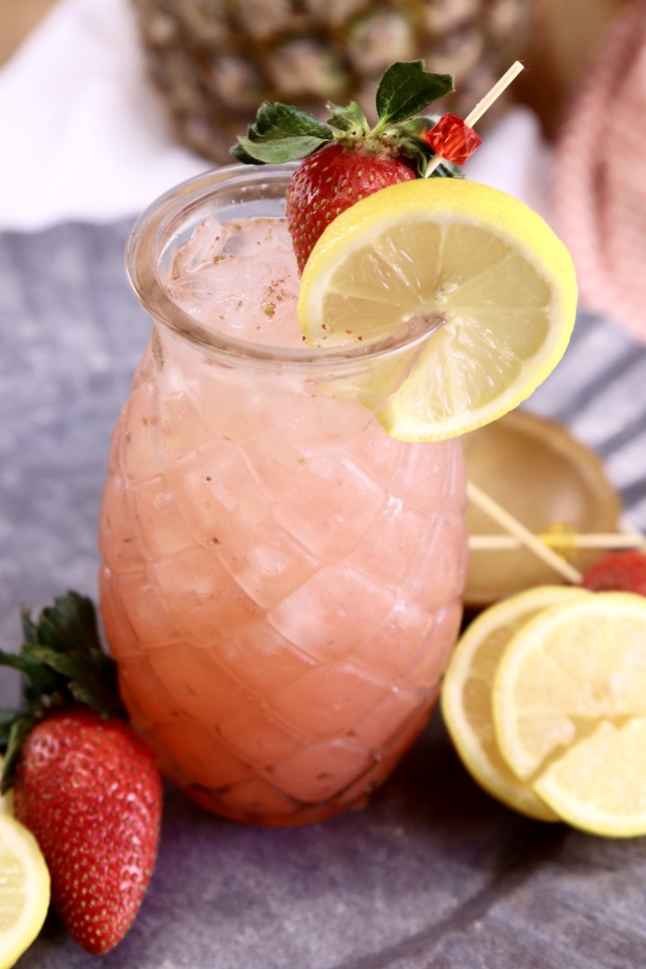 Pineapple shaped glass with pink cocktail, lemon slice and fresh strawberry garnish