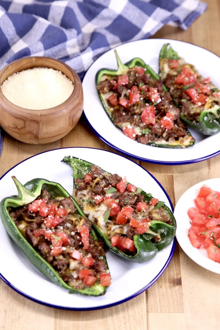 Plates of stuffed peppers topped with tomatoes