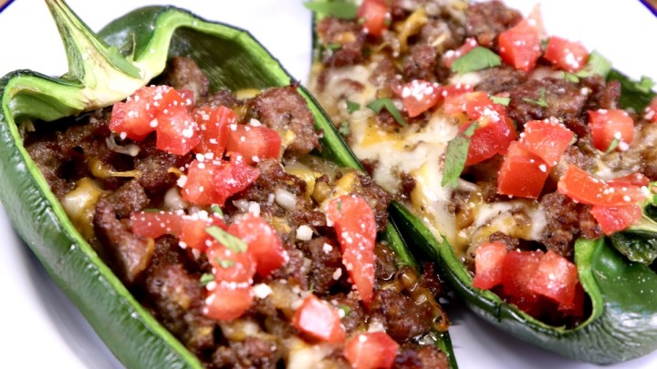 Sausage & Cheese Stuffed Poblano Peppers topped with diced tomatoes on a plate