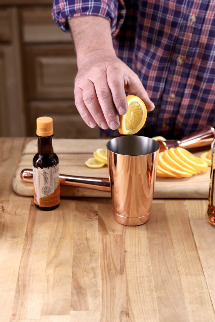 making cocktails with fresh orange - placing into a cocktail shaker