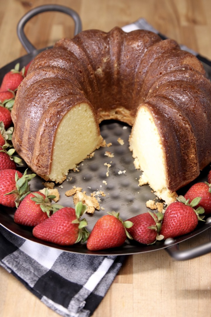 pound cake on a platter, 2 slices removed - strawberries surrounding cake