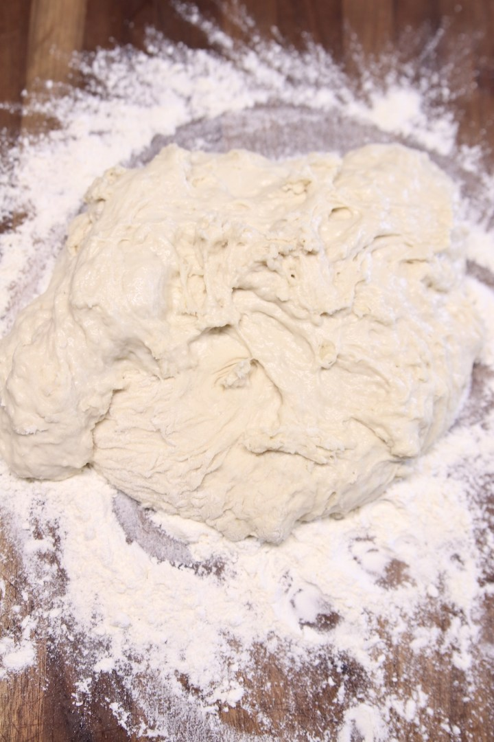 pizza dough on a floured board for kneading