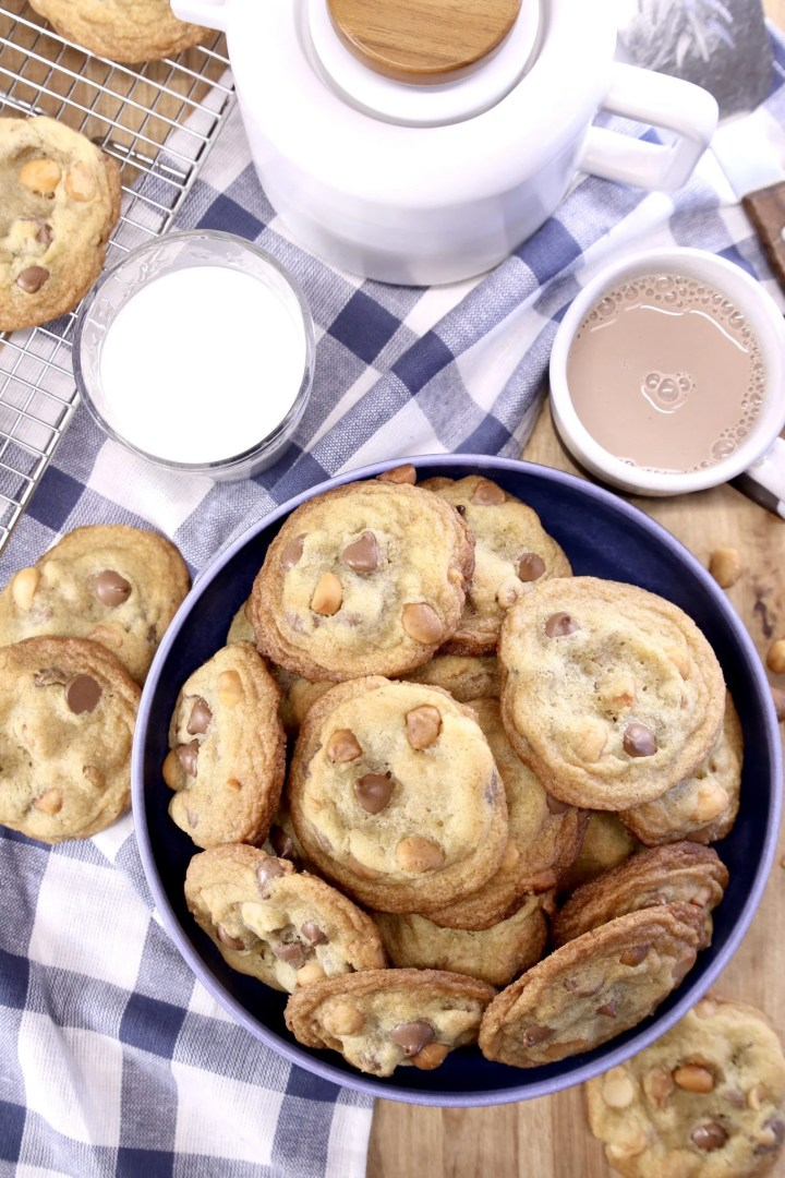 bowl of chocolate chip cookies with glass of milk, cup of hot chocolate