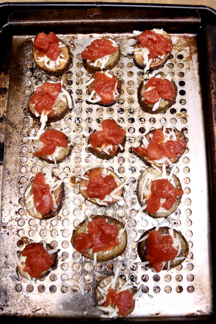 pan of potatoes topped with mozzarella and diced tomatoes
