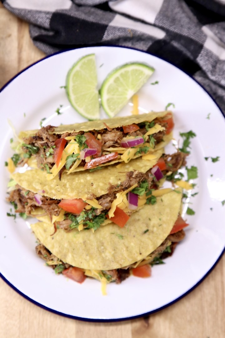 plate of 3 tacos with slices of lime