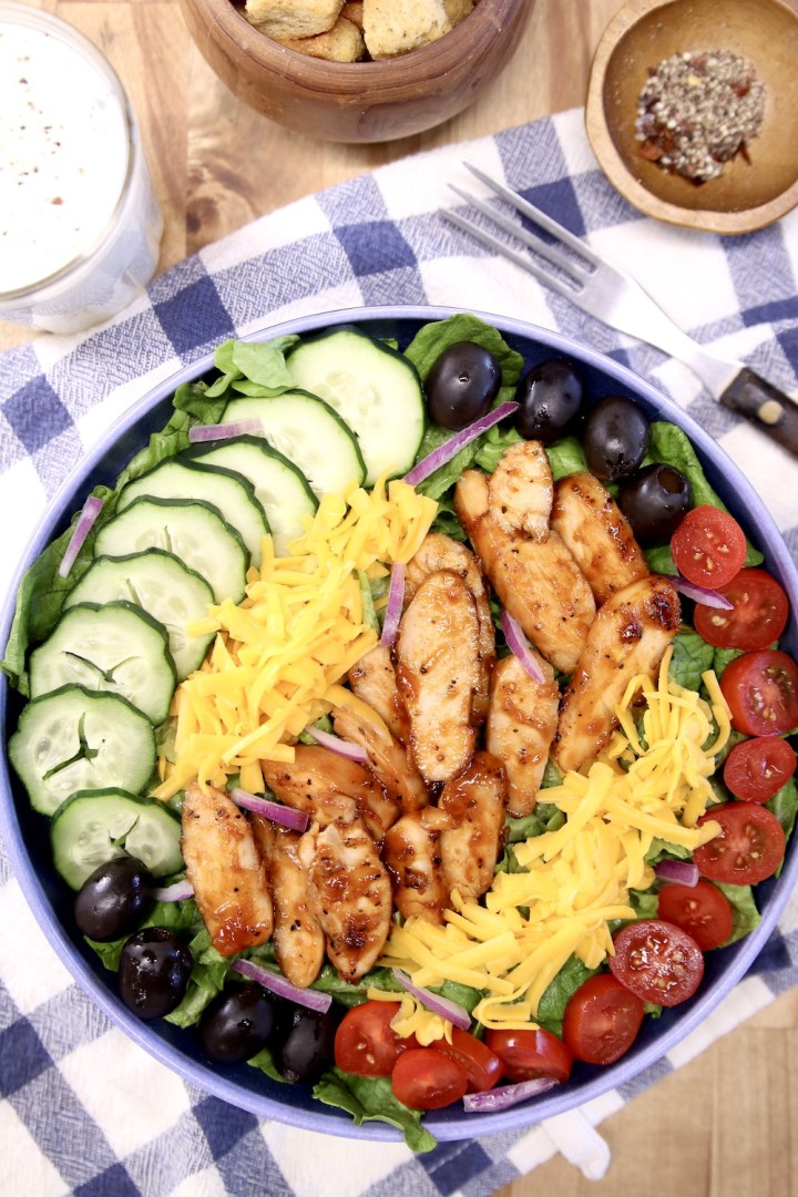 bbq chicken salad with cucumbers, tomatoes, black olives and cheese