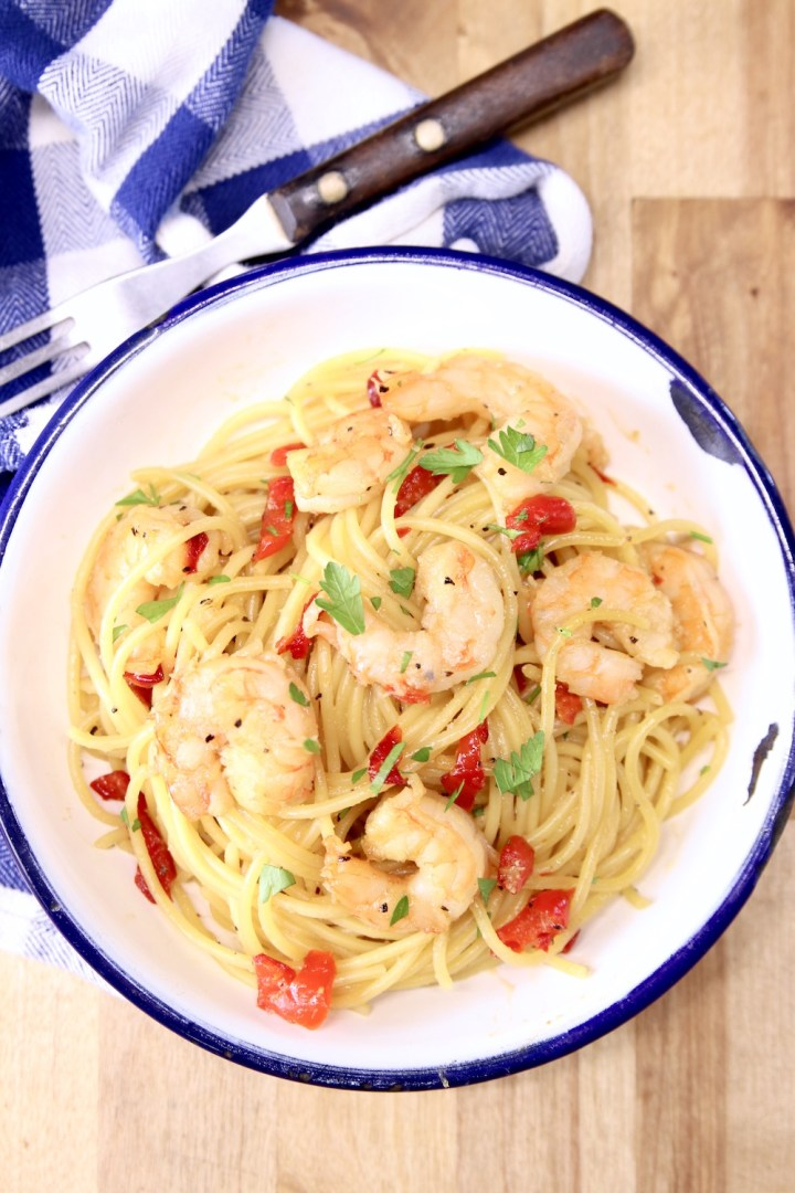 Honey Garlic Shrimp Spaghetti served in a bowl with a fork and blue check napkin