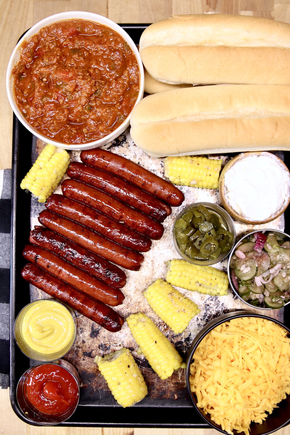Baking sheet with hot dog chili, buns, grilled hot dogs, corn on the cob, shredded cheese, condiments
